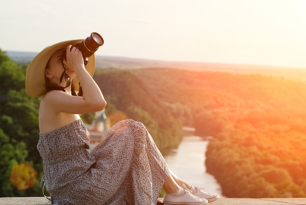 Dziewczyna siedzi i robi zdjęcia na tle lasu i meandrującej rzeki