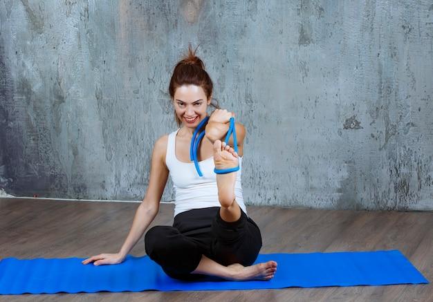 Dziewczyna siedzi i rozciąga mięśnie nóg z niebieską liną stretch.
