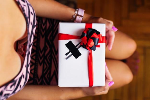 Dziewczyna siedzi i trzyma na kolanach białe pudełko z prezentem