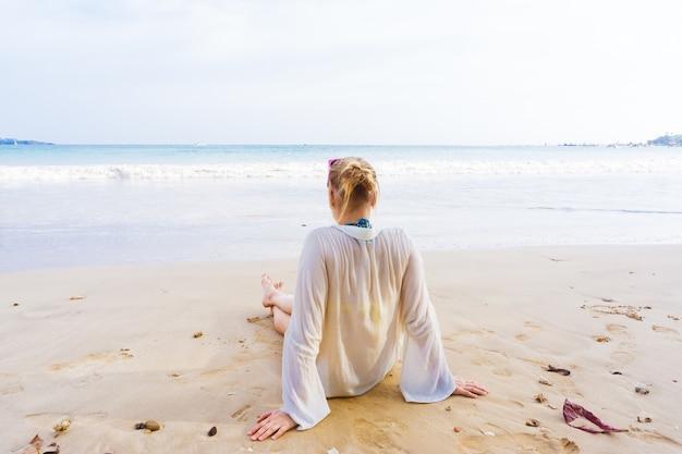 Dziewczyna siedzi na brzegu i patrzy w morze
