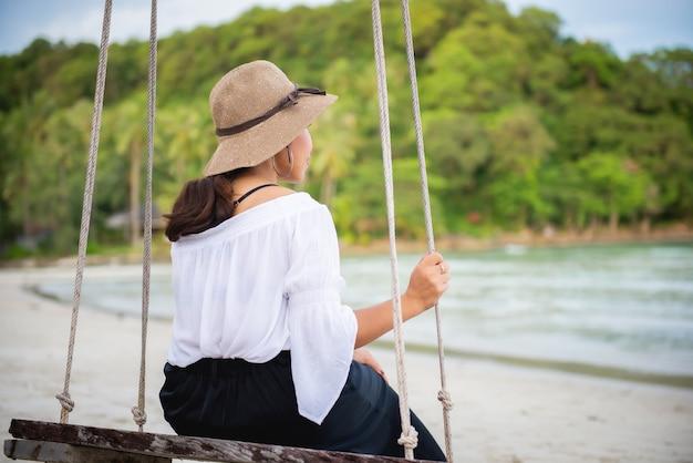 Dziewczyna siedzi na cichej huśtawce na plaży