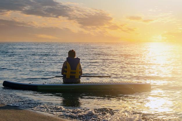 Dziewczyna siedzi na desce sup po uprawianiu sportów w oceanie w promieniach zachodzącego słońca