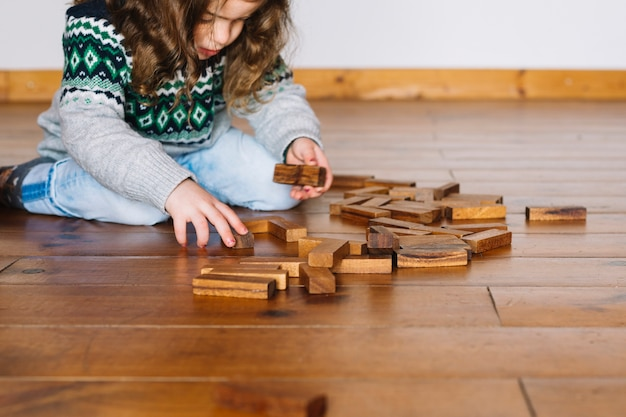 Dziewczyna siedzi na drewnianej podłodze gry jenga