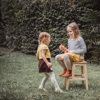 Dziewczyna siedzi na drewnianym krześle i trzyma małe dyniowe lampiony jack o.