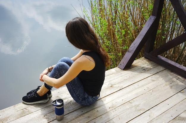 Dziewczyna siedzi na drewnianym molo w pobliżu wody.