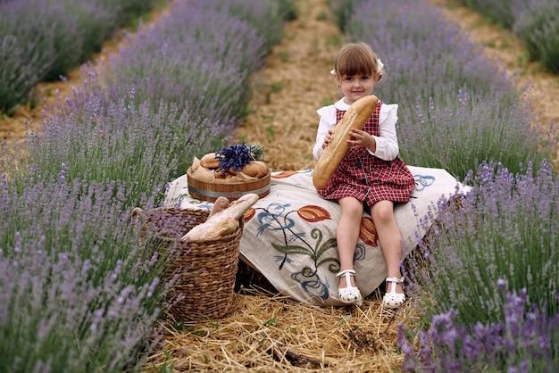 Dziewczyna siedzi na haftowanym obrusie i je chleb.