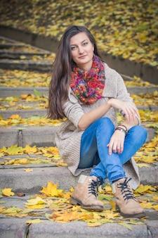 Dziewczyna siedzi na kamiennych schodach