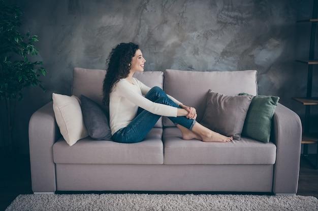 Dziewczyna siedzi na kanapie spędzając dzień w nowoczesnym stylu industrialnym loft w salonie w pomieszczeniu