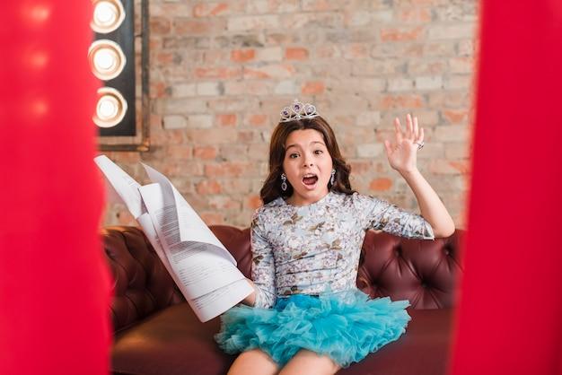 Dziewczyna siedzi na kanapie, trzymając się scenariuszy
