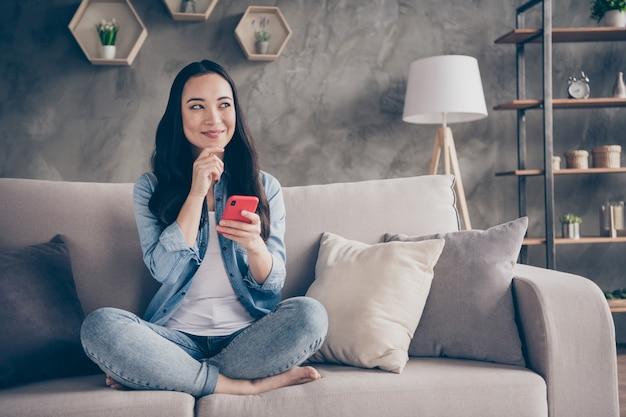 Dziewczyna siedzi na kanapie trzymając telefon