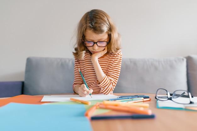 Dziewczyna siedzi na kanapie w domu rysuje pisze ołówkiem na papierze.