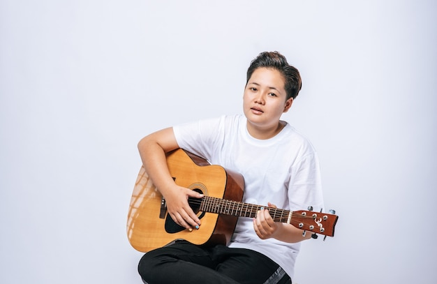 Dziewczyna siedzi na krześle i gra na gitarze.