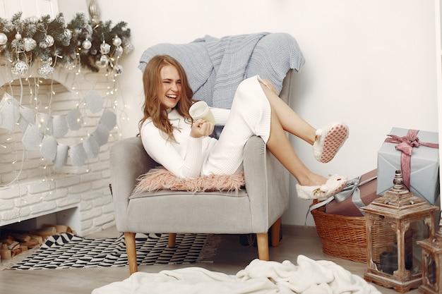 Dziewczyna siedzi na krześle. kobieta z kubkiem. pani przygotowuje się do świąt.