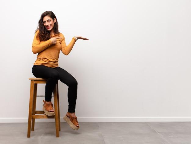 Dziewczyna siedzi na krześle, wskazując na obiekt trzymany w ręku