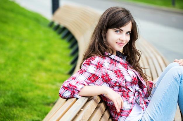 Dziewczyna siedzi na ławce na świeżym powietrzu