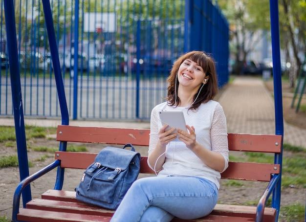 Dziewczyna siedzi na ławce z tabletem i śmieje się, patrząc w kamerę. brunetki dziewczyna w białej kurtce i cajgach na ulicie. odległa komunikacja w kwarantannie.