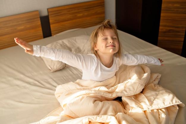 Dziewczyna siedzi na łóżku we wczesnym porannym słońcu i rozciąga się, energia na dzień dobry, dobry zdrowy sen