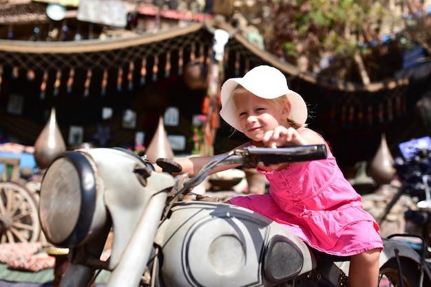 Dziewczyna siedzi na motocyklu retro i śmiejąc się