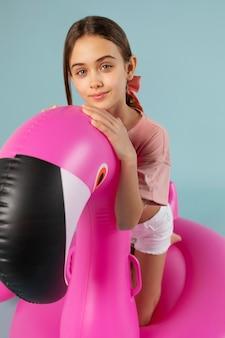 Dziewczyna siedzi na nadmuchiwanym flamingu