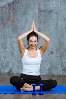 Dziewczyna siedzi na niebieski mat do jogi w pozycji lotosu i medytacji.