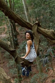 Dziewczyna siedzi na ogromnej gałęzi drzewa liany w dżungli.