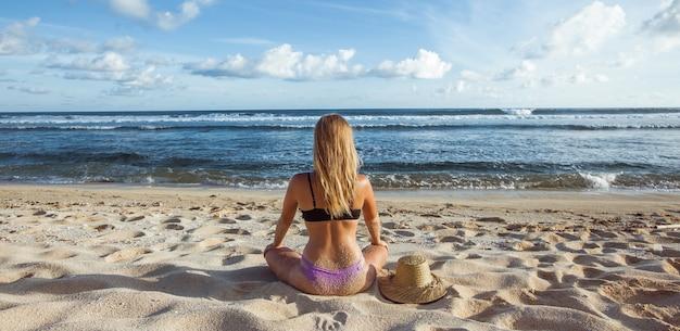Dziewczyna siedzi na piasku widok z tyłu i patrząc na ocean banner panorama