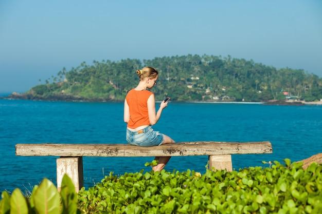 Dziewczyna siedzi na plaży i patrzy na telefon komórkowy
