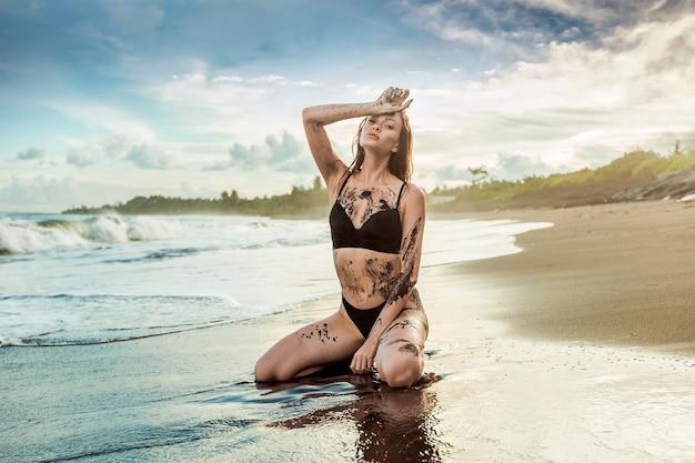 Dziewczyna siedzi na plaży i posmarowana czarnym piaskiem