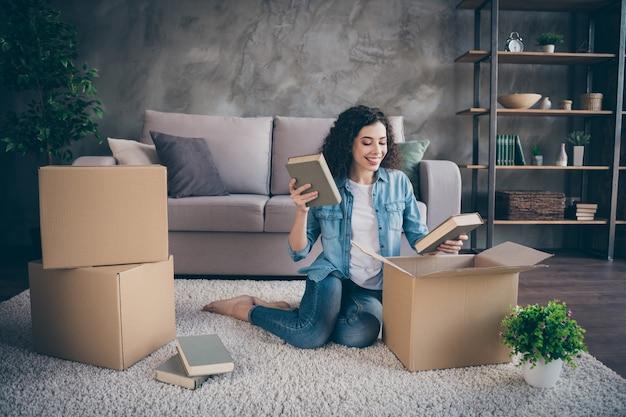 Dziewczyna siedzi na podłodze dywan pakowanie rzeczy zakupy w nowoczesnym stylu loft industrialny salon