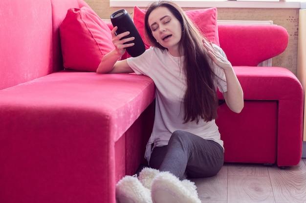 Dziewczyna siedzi na podłodze i słucha muzyki z przenośnego głośnika