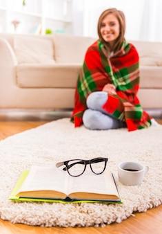 Dziewczyna siedzi na podłodze pokryte kocem i uśmiechnięte.
