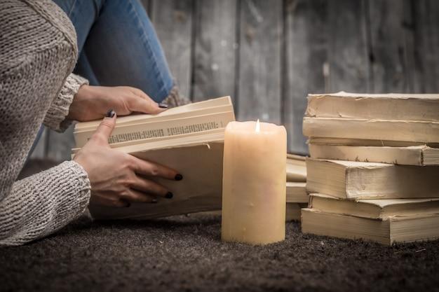 Dziewczyna siedzi na podłodze w otoczeniu wielu białych książek i dużej świecy