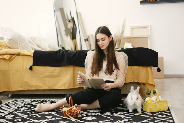Dziewczyna siedzi na podłodze z książką w otoczeniu tematów wielkanocnych.