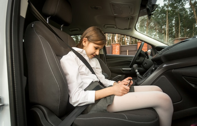 Dziewczyna siedzi na przednim siedzeniu samochodu i korzysta z telefonu komórkowego