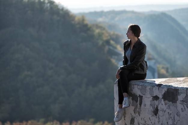 Dziewczyna siedzi na przyrodę. stopy na klifie. niezależna podróż.