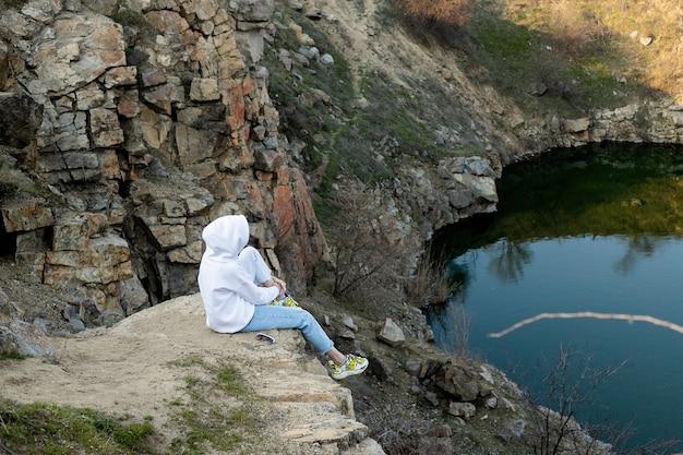 Dziewczyna siedzi na skraju góry w białej bluzie z kapturem i patrzy na jezioro