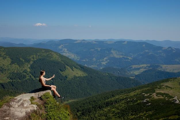 Dziewczyna siedzi na skraju klifu i spogląda na słoneczną dolinę i góry