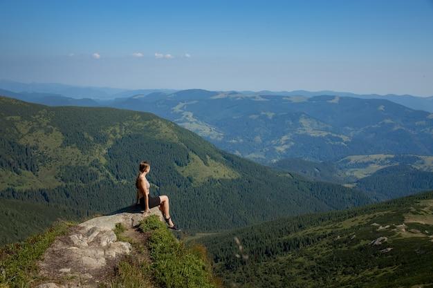 Dziewczyna siedzi na skraju klifu i spogląda na słoneczną dolinę i góry.