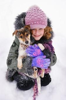 Dziewczyna siedzi na śniegu i trzyma w rękach swojego ukochanego psa. szczęśliwe dzieciństwo. miłość do zwierząt