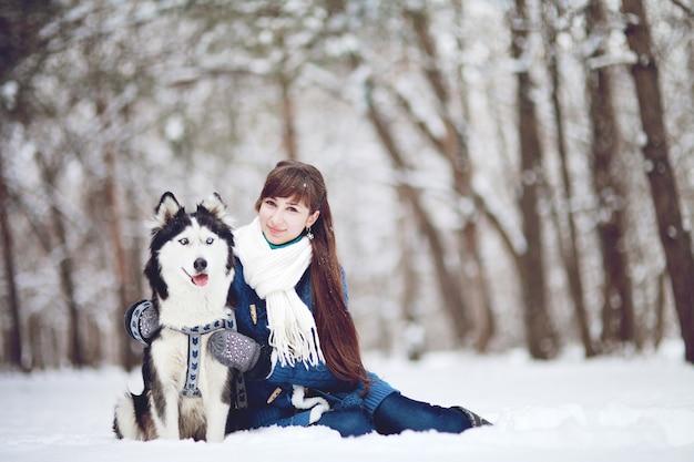 Dziewczyna siedzi na śniegu z psem husky syberyjski w zimowym lesie