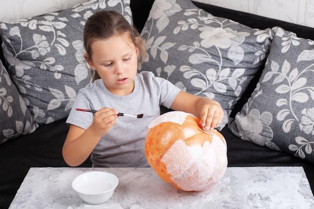 Dziewczyna siedzi na sofie i przykleja serwetki do balonu, wystrój dyni na halloween.