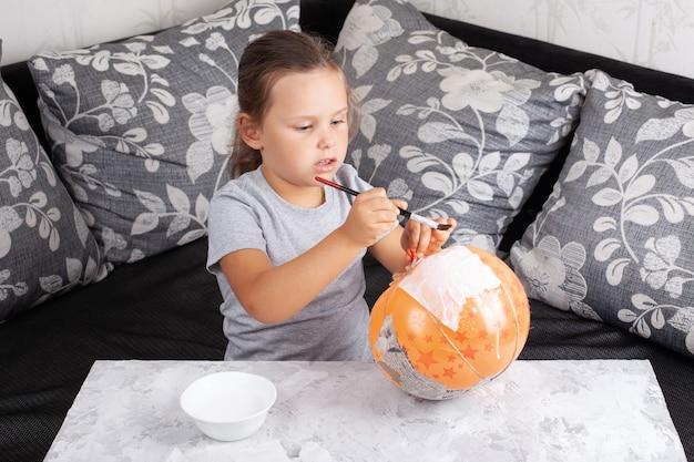 Dziewczyna siedzi na sofie i przykleja serwetki do balonu, wystrój z dyni halloween w salonie.