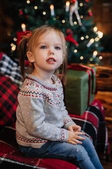 Dziewczyna siedzi na sofie w pobliżu drzewa noworocznego