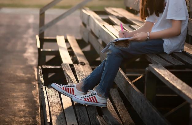 Dziewczyna siedzi na starych drewnianych trybunach.