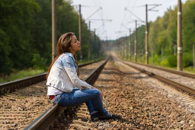 Dziewczyna siedzi na szynach i zamyślona patrzy w niebo.