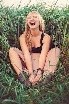 Dziewczyna siedzi na trawie i śmiejąc się. roześmiana dziewczyna przyjemność. stonowany w ciepłych kolorach. zabytkowy styl. hipster dziewczyna.