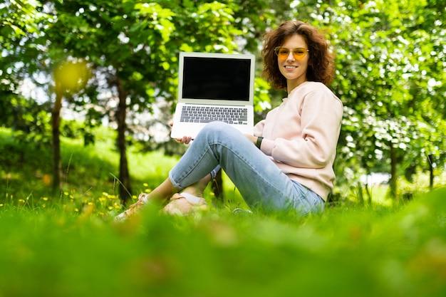 Dziewczyna siedzi na trawie w letnim parku, trzymając laptopa z ekranem do przodu z układem