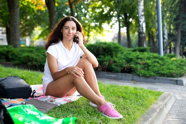 Dziewczyna siedzi na trawie w parku i komunikuje się przez telefon