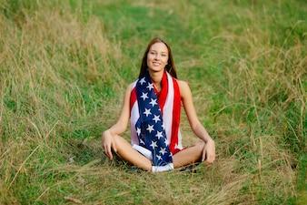 Dziewczyna siedzi na trawie z amerykańską flagą