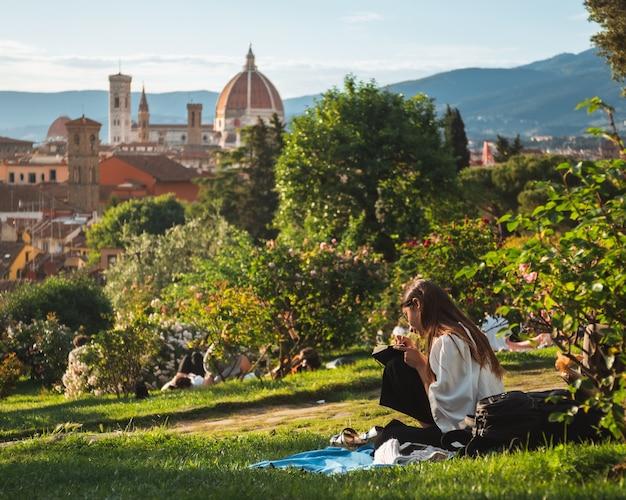 Dziewczyna siedzi na trawie z pięknym widokiem na florencję